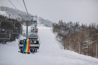 A rainbow flag hanging from a loaded chair of snowboarders.