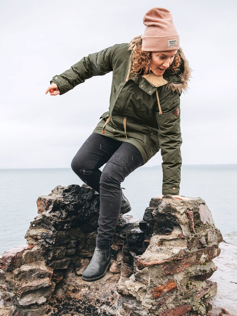 A woman wearing a Burton Saxton jacket and climbing on rocks in the rain.