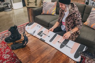 Female Burton Employee Looking at Stick Shift Snowboard