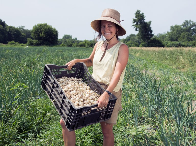 Woman holding basket full of onions