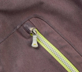 Close up of the fabric worn down on the men's AK Stagger pants pocket zipper.
